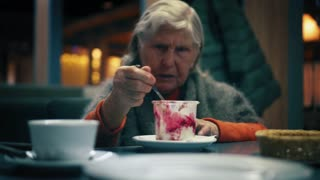Intelligent elderly woman is eating strawberry ice-cream in cafe and talking to someone