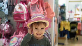 Little boy dresses hat in shop and smiles. Portrait. Kids shopping