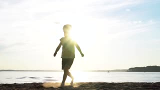 Little boy running on the beach kicking sand at sunset