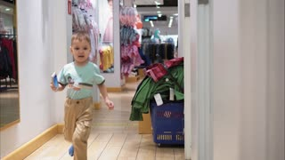 Little boy runs to meet his mom in the store and have fun