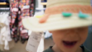 Little boy trying on a hat in a store and smiling. Kids shopping