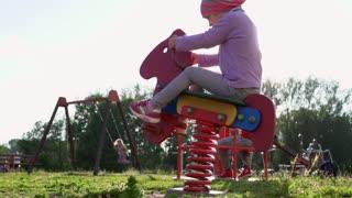 Little girl rides carousel on playground. Slow mo