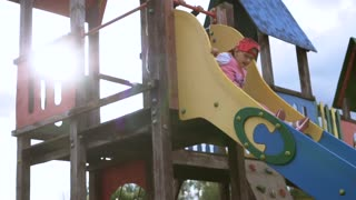 Little girl sliding down children's slide rises to her feet and runs away. Slow motion