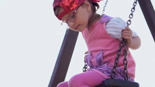 Little girl swinging. Slow Motion