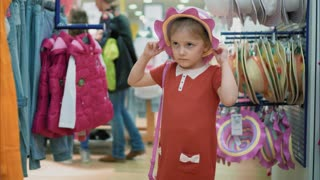 Little girl try on a hat and bag in a store, have fun and smiling. Kids shopping