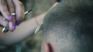 Male is hairstyling and haircutting in a barber shop or hair salon. Close up view on female barber's hands cut hair with scissors. Slow motion.