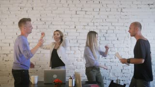 Office workers celebrate victory, dance, throw up paper and have fun. Coworking. Slow motion
