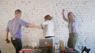 Office workers dance, celebrate the victory, fail to throw the paper, laugh and have fun. Coworking. Slow motion