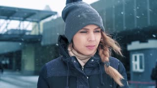 Portrait footage of beautiful woman standing outdoors in winter and watching snow fall. Slow mo