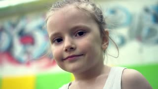 Portrait of a little girl in a stylish gymnastic center