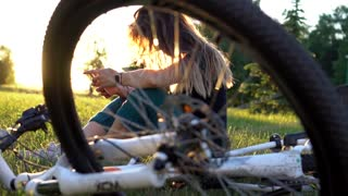 Pretty woman browses web using app on smartphone in city park at sunset. Bike close up. Slow mo