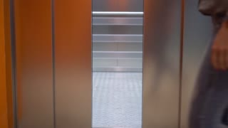 Pretty woman enters the elevator. Close-up of legs