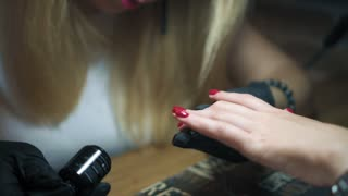 Professional manicure procedure in nail salon. Close up female hands, covering of transparent enamel and nail varnish