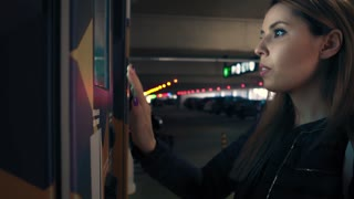 Stylish businesswoman enters the data on terminal at parking and makes payment. Female is touching an electronic screen on terminal
