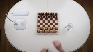 The couple plays chess. The girl loses the game and throws figures. Top view. Hands close up view