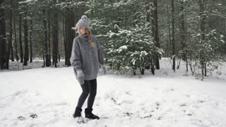The guy catches up with the girl after playing snowballs and shakes herself off the snow. Slow mo