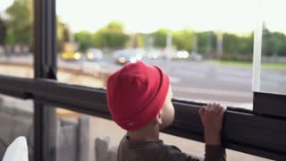 The little boy looks at cars passing by. Urban bustle
