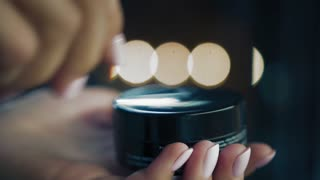 Well-groomed woman's hands open a beauty product and shows it to the camera. Female softly open metallic jar of cream. Closeup, Slow mo