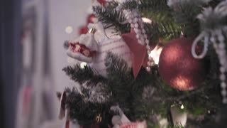 Woman decorates Christmas tree with toys. Christmas tree, toys and hands close-up view