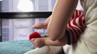 Woman dressed in white is sitting on the bed and carefully holding cute little baby in front of the panoramic window. close-up