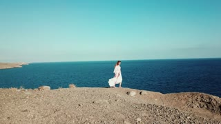 Woman is walking on the top of the rock near the ocean and raising her hands enjoying summer vacation travel. Amazing ocean landscape with blue sky.