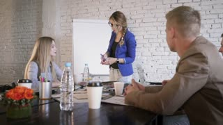 Woman leader gives presentation. Female manager presents new project plan to colleagues at business meeting. Businesswoman explaining ideas on flip chart to coworkers in office