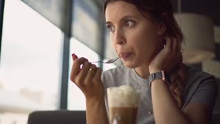 Woman tastes and drink coffee with cream