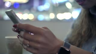Woman uses smart phone in cafe. Close-up hands. Dolly shot