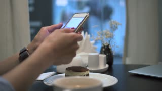 Woman using app on smartphone in coffee shop