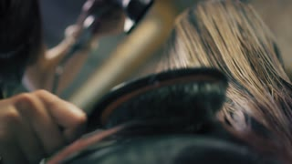 Woman with long blonde hair is sitting in hair salon while hairdresser is drying her wet hair with hair dryer and hairbrush, Closeup, down back angle. Slow mo.