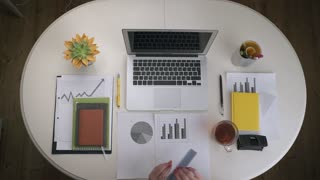 Woman working with a business graph and a laptop that stands on a white table with a couple tea. Top view. Hands close up