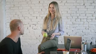 Work in a creative office. Young girl sitting at desk next to business partner playing with green apple communicates and smiling. Employees say hello and shake hands