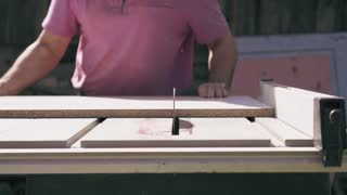 Worker is doing joinery works on circular saw colseup view. Man cuts wood boards with rotated blade and then goes away. Slow motion