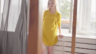 Young attractive blond woman on yellow dress standing near the window smiling and straightening hair
