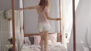 Young attractive brunette in pajamas dancing on bed in her bedroom