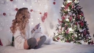 Young beautiful woman gives a Christmas gift to a man near a Christmas tree