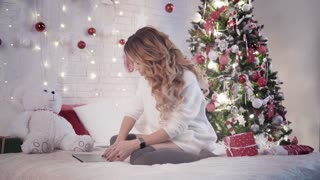 Young beautiful woman types on a laptop on a bed near a christmas tree