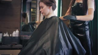 Young blonde woman is sitting in chair in beauty salon while hairdresser is straightening a cape and unties her long hair