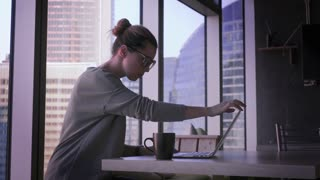 Young business woman in glasses is working on laptop in office. Beautiful female with computer in business center