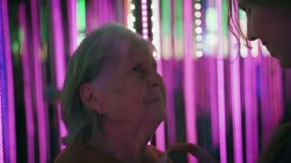 Young female helps elderly woman to wear headphones. Adult lady is listening music in earphones, smiling and dansing in neon lights. Closeup. Slow mo.