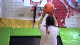 Young girl hits the ball in a basketball ring and is happy