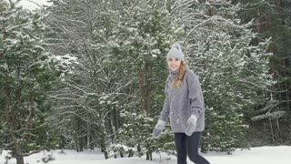 Young happy girl running and throwing snow into the camera in winter. Slow mo