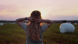 Young woman touches her long hair and turns at sunset. Slow Mo
