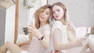 Young women friends make selfie with smartphone in the bedroom near the bed