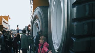 ZHODINO, BELARUS - SEPTEMBER 21, 2017. FACTORY OF QUARRY TRUCKS BELAZ. Closeup view on large rubber wheels of the biggest dump truck in the world. People walking around big tipper and taking photos