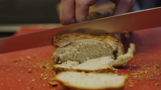 A Man Slicing A Bread In Kitchen