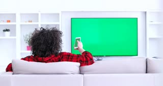 A Man Watches A Tv With A Green Screen In A Cozy Living Room