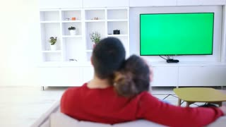 A Young Couple Watches A Tv With A Green Screen In A Cozy Living Room