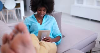 African American Woman Using Tablet Computer On Couch