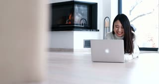 Asian Woman Laying On The Floor Using Laptop To Surf Online